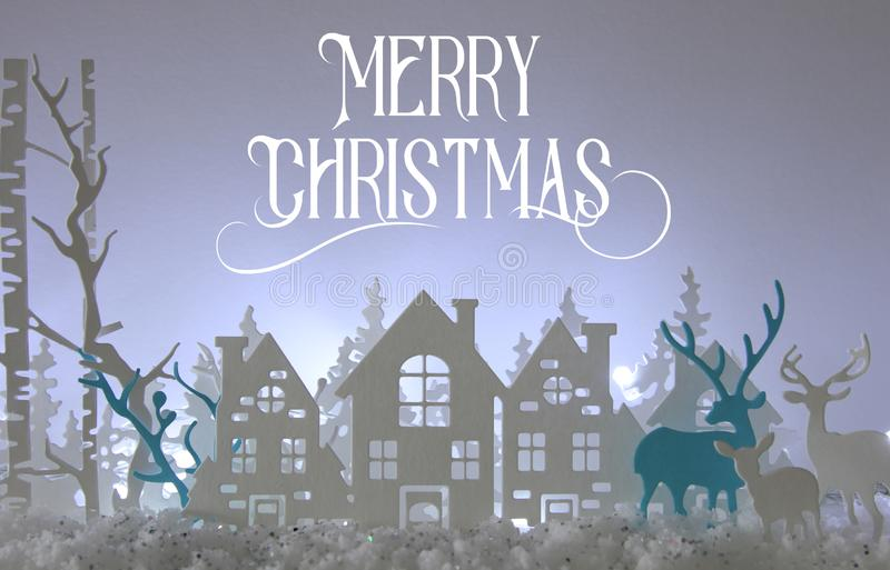 Magical Christmas paper cut winter background landscape with houses, trees, deer and snow in front of white lights background. vector illustration