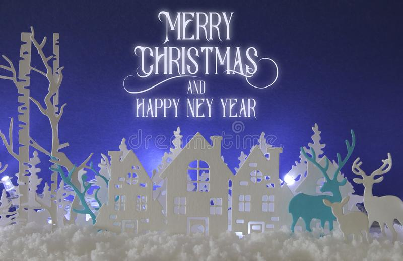 Magical Christmas paper cut winter background landscape with houses, trees, deer and snow in front of white lights background. Magical Christmas paper cut royalty free stock images