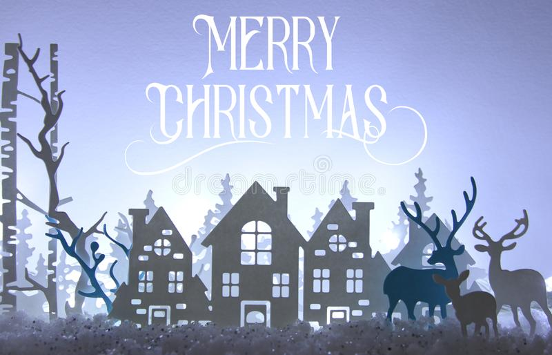 Magical Christmas paper cut winter background landscape with houses, trees, deer and snow in front of white lights background. Magical Christmas paper cut royalty free stock photo