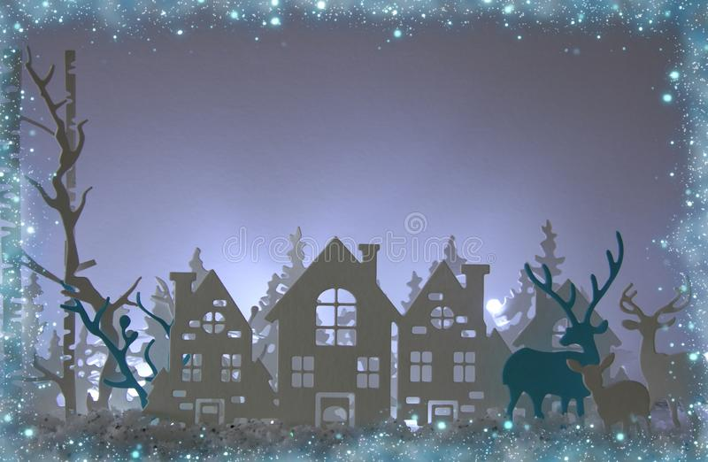 Magical Christmas paper cut winter background landscape with houses, trees, deer and snow in front of white lights background. Magical Christmas paper cut stock photography