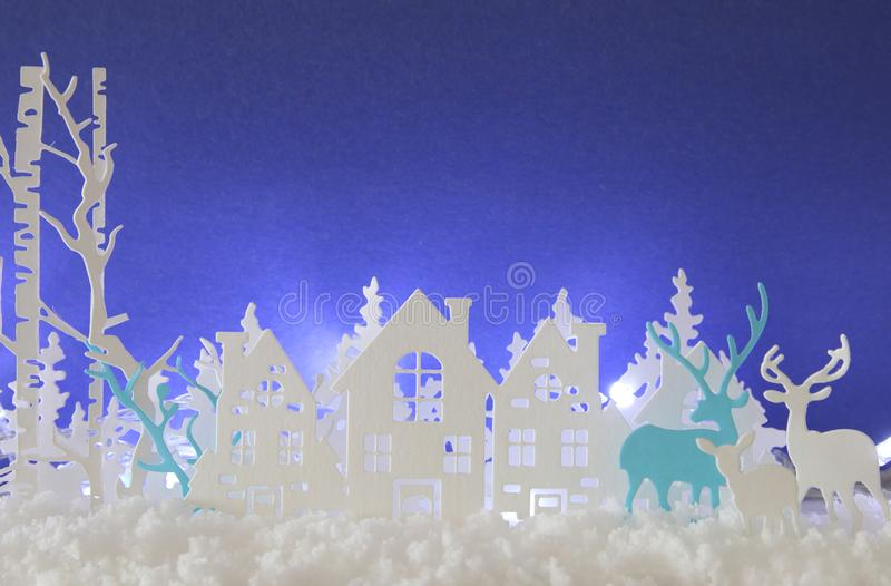 Magical Christmas paper cut winter background landscape with houses, trees, deer and snow in front of white lights background. Magical Christmas paper cut royalty free stock photography