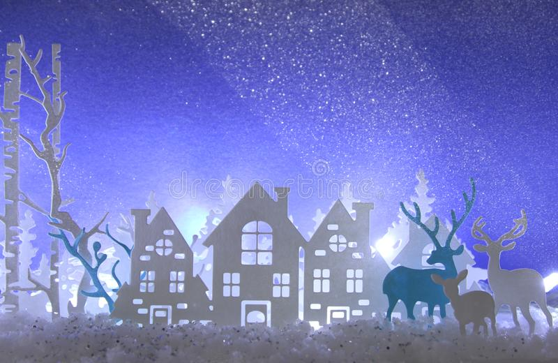 Magical Christmas paper cut winter background landscape with houses, trees, deer and snow in front of white lights background. Magical Christmas paper cut stock image