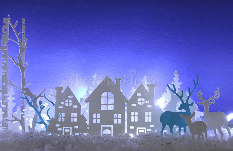 Magical Christmas paper cut winter background landscape with houses, trees, deer and snow in front of white lights background. Magical Christmas paper cut stock images
