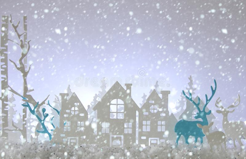 Magical Christmas paper cut winter background landscape with houses, trees, deer and snow in front of white lights background. Magical Christmas paper cut stock photo
