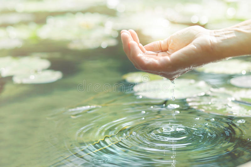 Magical contact between human hand and water stock photography