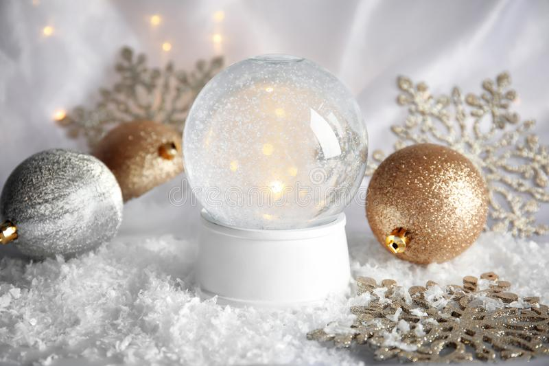 Magical empty snow globe with Christmas decorations. On white fabric royalty free stock image