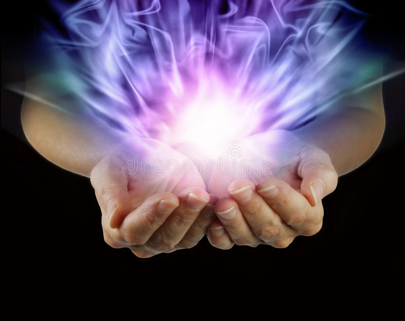Magical Energy Formation. Woman with outstretched cupped hands with healing energy emanating from hands on a black background stock image
