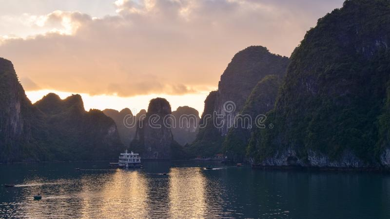 Magical golden sunset in Halong Bay in Vietnam, South China Sea. Cruise Sails liner ship wooden junk sailing rock islands the royalty free stock image