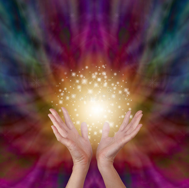 Magical healing energy on radiating color background. Female healer's hands outstretched open with a beautiful sparkling ball of golden light above on a deep royalty free stock image