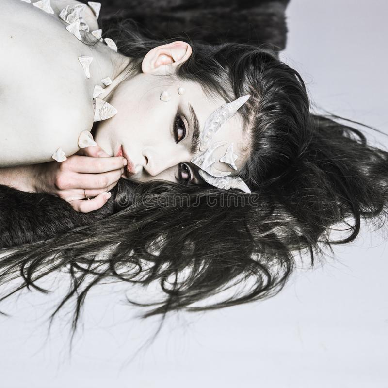Magical horror female creature lay light background. Halloween fictional creature make up long hair. Woman make up demon. Beast halloween celebrate. Demon with stock photo