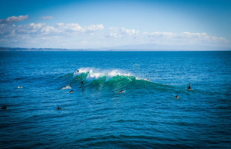 The magical huge waves in the bay of santa cruz make this a surf. Santa Cruz, United States - January 27 , 2013 :  Surf capitol of the US. Only the bravest stock photo