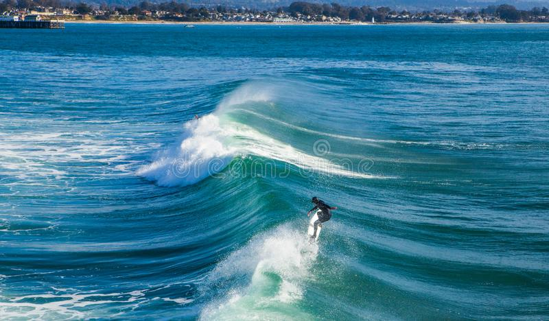 The magical huge waves in the bay of santa cruz that are rolling. Santa Cruz, United States - January 27 , 2013 :  Surf capitol off the US. Only the bravest stock photography