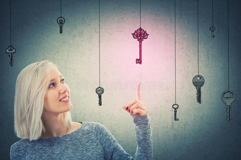 Magical key. Young woman pointing finger to a magic purple key to success. Concept of business aspirations, achievement and the right choice. Business challenge stock photography