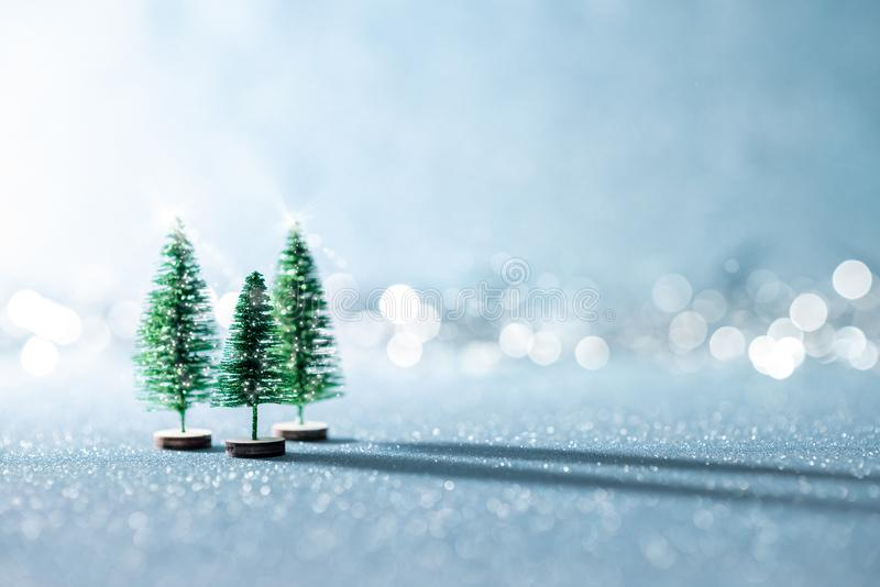 Magical miniature winter wonderland background. Evergreen christmas trees on shiny blue background with bokeh. stock photos