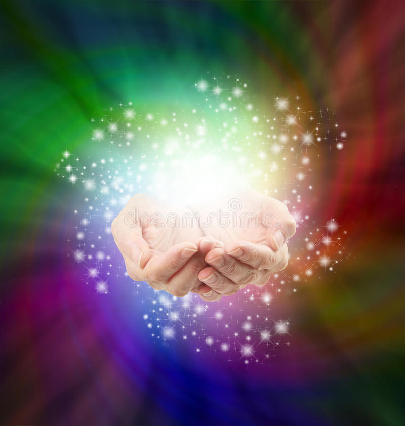 Magical Moment. Female cupped hands emerging from a spiraling dark multicolored background with a twirl of sparkles all around depicting magic and spells royalty free stock photos