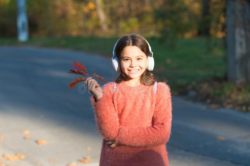 Magical moments start with music. Adorable girl enjoy music on autumn landscape. Cute little child listen to music. Playing in stereo headphones. Music royalty free stock images