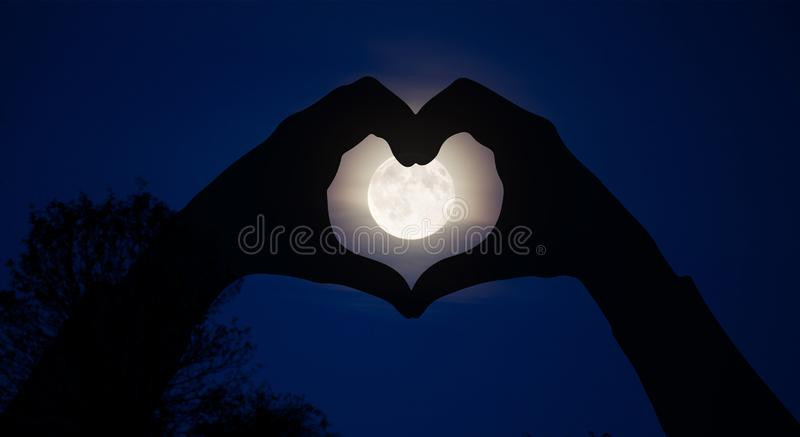 Magical moon energy healing universal energy, heart hands. Hands silhouette making heart shape over full moon Magical energy healing , dreams, wish, blessing royalty free stock image