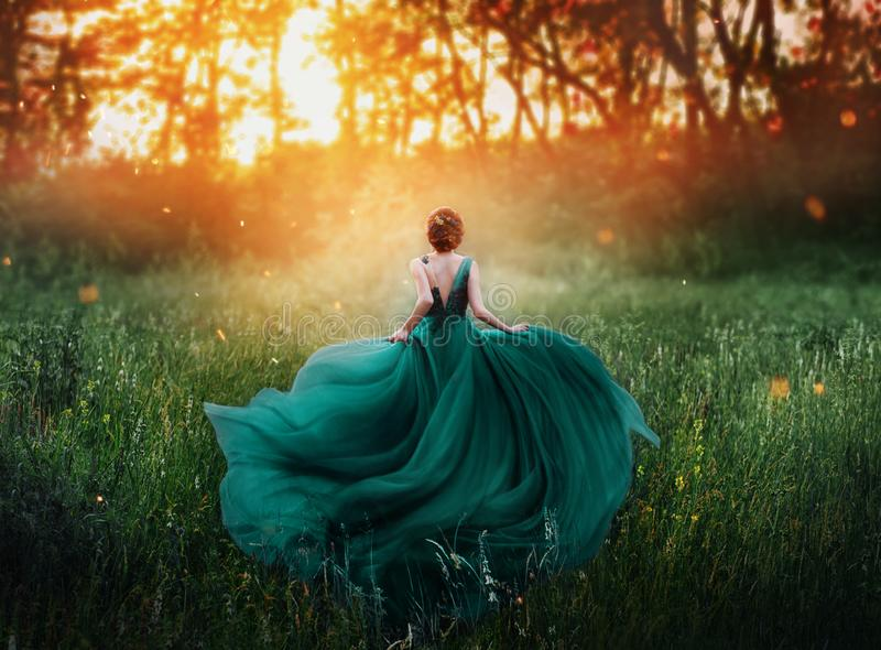 Magical picture, girl with red hair runs into dark mysterious forest, lady in long elegant royal expensive emerald green. Turquoise dress with flying train stock image