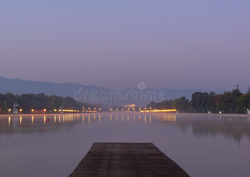 Magical purple sunrise and view of a wooden pier in the mirrored water of the Rowing Canal in Plovdiv, Bulgaria stock images