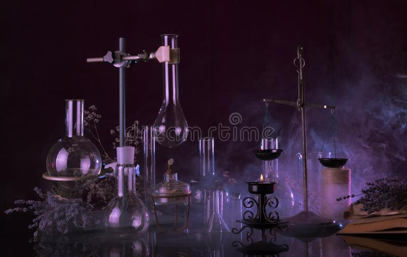 Magical quackery ritual. Glass flasks, lit a candle and ancient book in mysterious smoke stock images