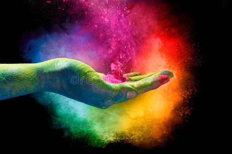 Magical rainbow colored dust exploding from a hand. Holi Festival. Magical rainbow colored powder exploding from the palm of a cupped hand creating a vibrant stock photos