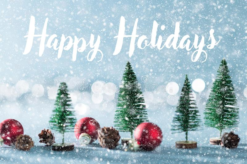 Magical snowy miniature winter wonderland background. Evergreen trees, pine cones and red christmas baubles on shiny background. stock images