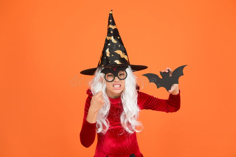 Magical spell. Small witch with white hair. Wizard or magician. Halloween party. Photo booth props. Small girl in black. Witch hat. Autumn holiday. Join stock photos