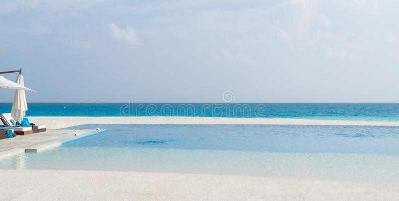 Deck chairs and infinity pool over amazing tropical lagoon in Maldives royalty free stock photos