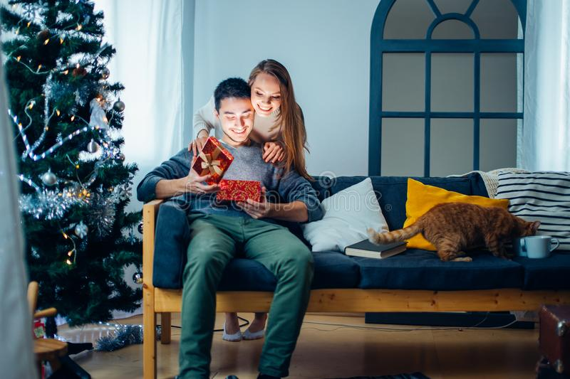 Magically surprise in box. man open christmas gift. Woman opening gift box and smiling while her boyfriend sitting close to her on couch with Christmas royalty free stock photography