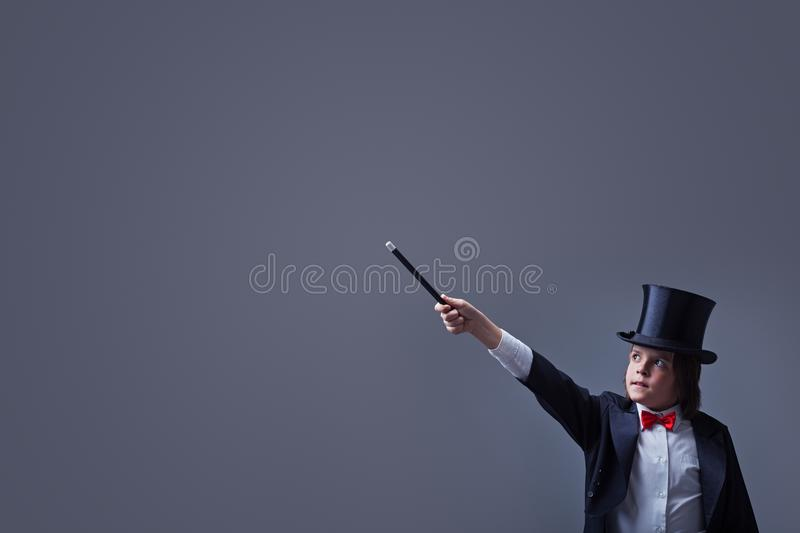 Magician boy with hardhat pointing to copy space with magic wand stock photo