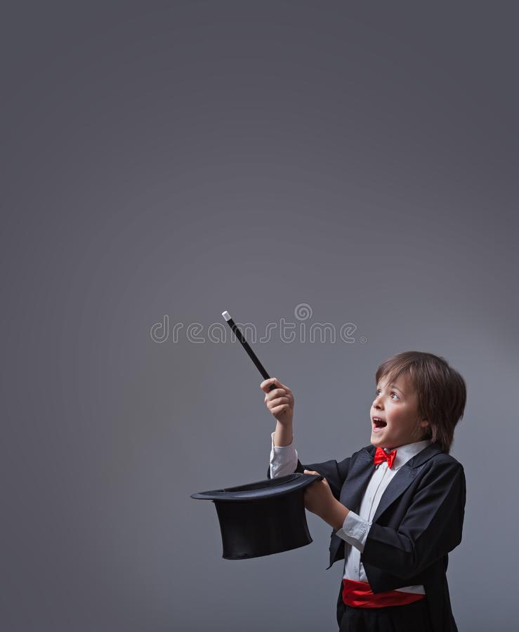 Magician boy performing with magic wand and hard hat royalty free stock photography