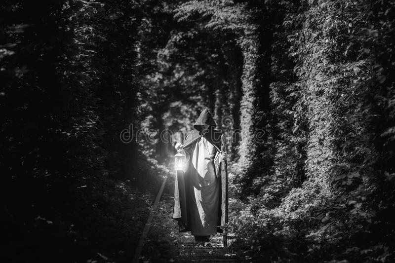 A magician in a cloak in a dark forest with a lantern. Black and white image. stock photography