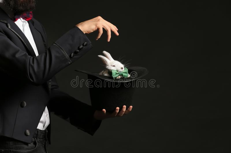 Magician holding hat with rabbit on dark background royalty free stock photo