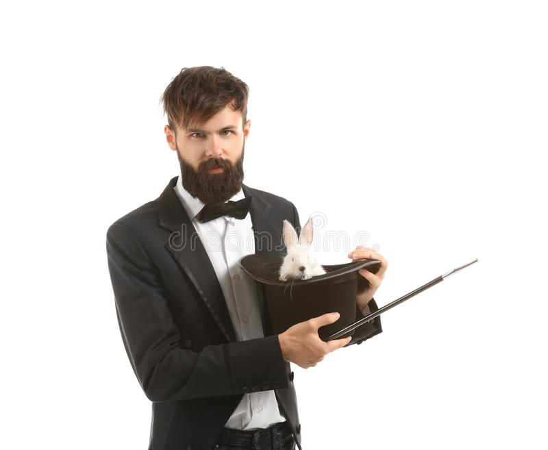 Magician holding hat with rabbit on white background stock photo