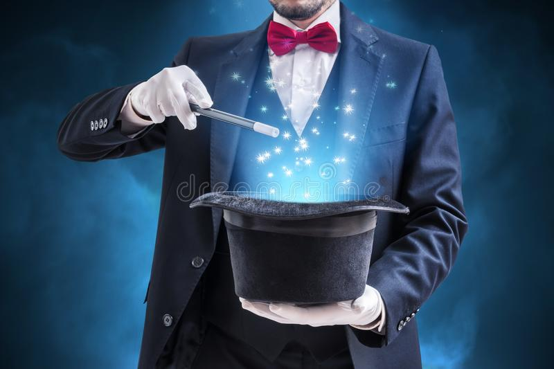 Magician or illusionist is showing magic trick. Blue stage light in background royalty free stock photos