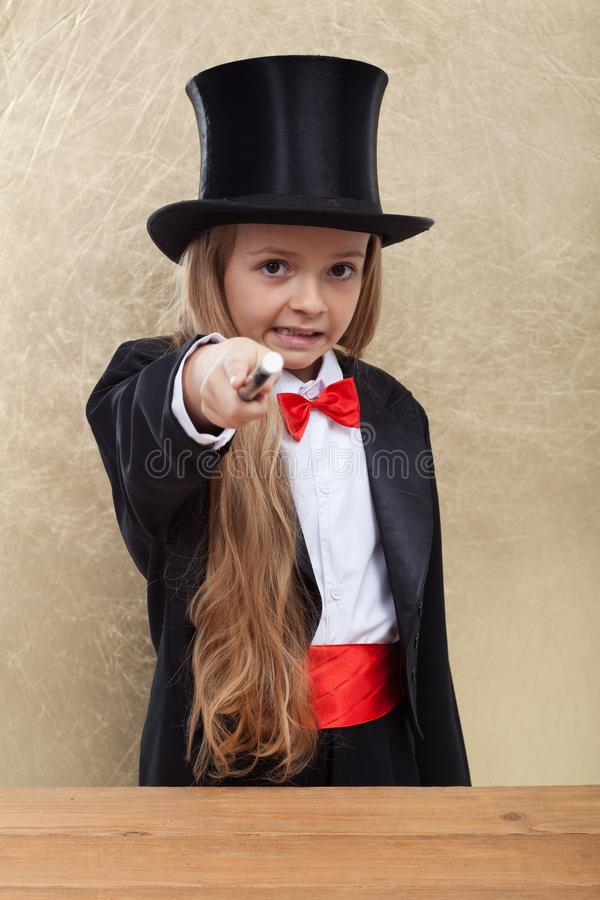 Magician little girl performing an evil magic trick - pointing with the wand to the viewer. And making a strange grimace royalty free stock photos