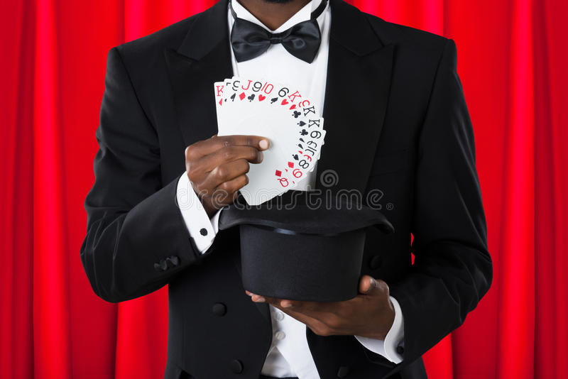 Magician With Playing Cards And Hat. Close-up Of A Male Magician With Playing Cards And Hat stock images