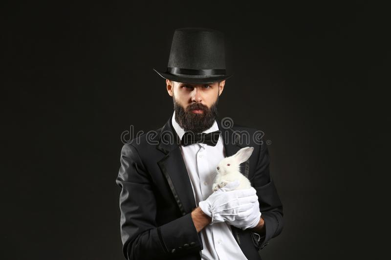 Magician with rabbit on dark background royalty free stock image