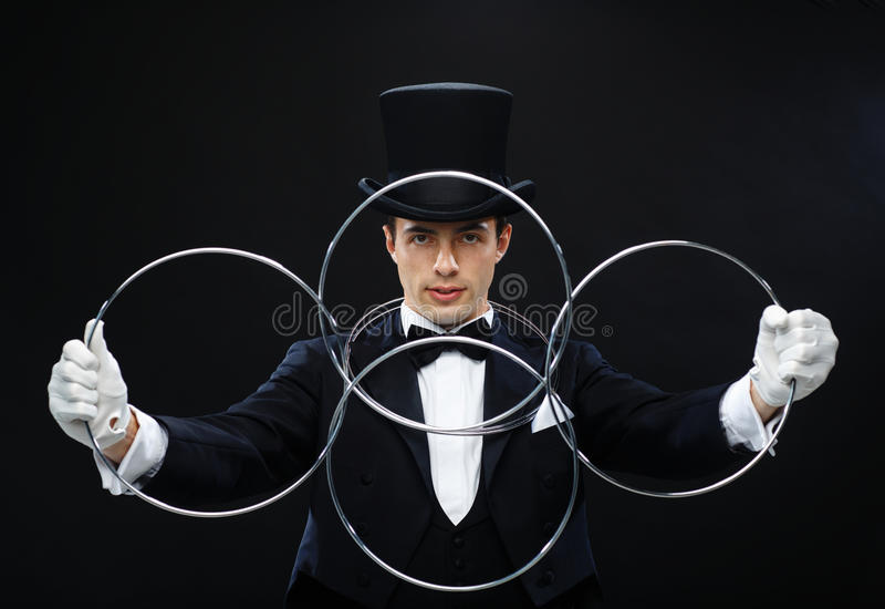 Magician showing trick with linking rings stock photos