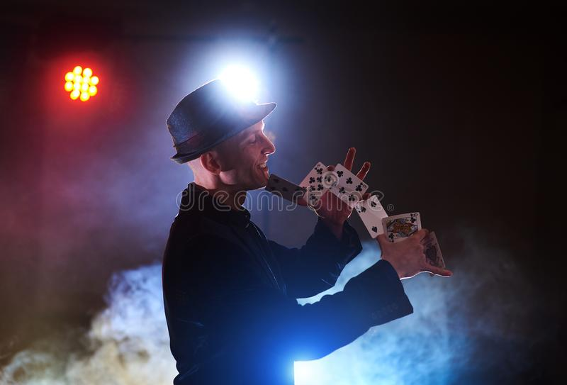 Magician showing trick with playing cards. Magic or dexterity, circus, gambling. Prestidigitator in dark room with fog royalty free stock images
