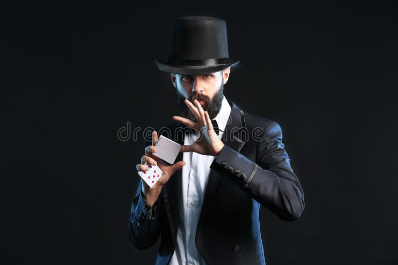 Magician showing tricks with cards on dark background royalty free stock photos