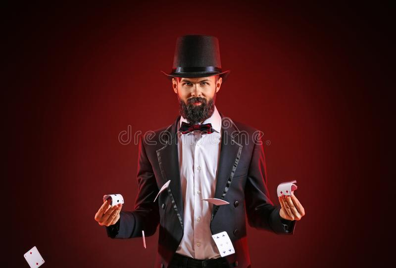 Magician showing tricks with cards on dark background stock photography