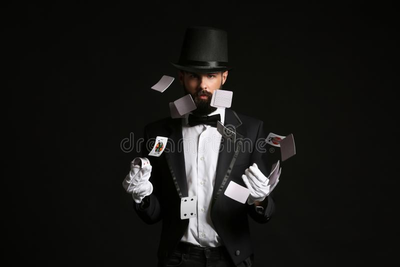 Magician showing tricks with cards on dark background royalty free stock photography