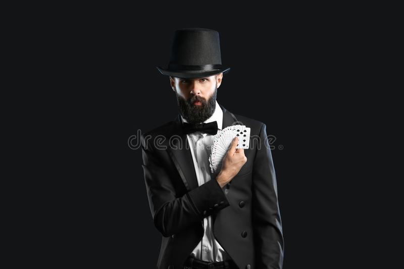 Magician showing tricks with cards on dark background stock image