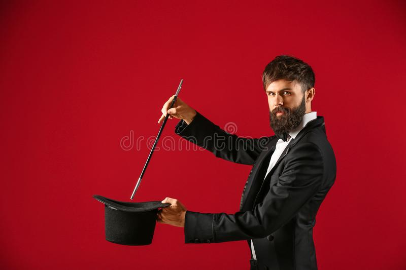 Magician showing tricks with hat on color background royalty free stock photo