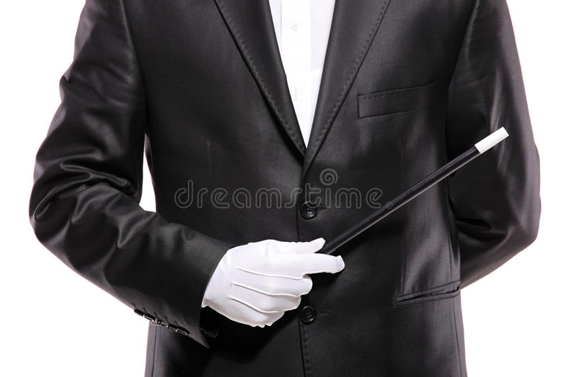 A magician in a suit holding a magic wand royalty free stock photos