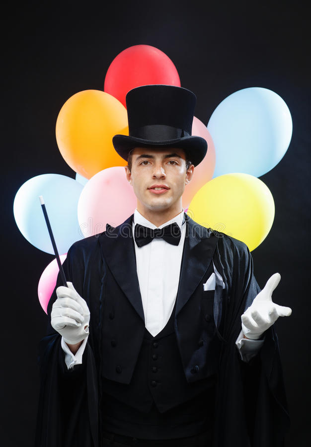 Magician in top hat with magic wand showing trick. Performance, circus, show, birthday party concept - magician in top hat with magic wand and colorful balloons royalty free stock photos
