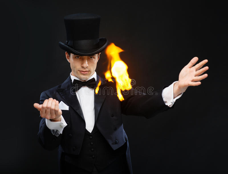 Magician in top hat showing trick with fire royalty free stock photo