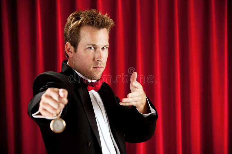 Magician: Using A Watch to Hypnotize royalty free stock photography