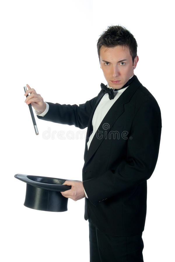 Magician with wand and hat. Young handsome magician holding his hat and magic wand during show isolated on white royalty free stock photo
